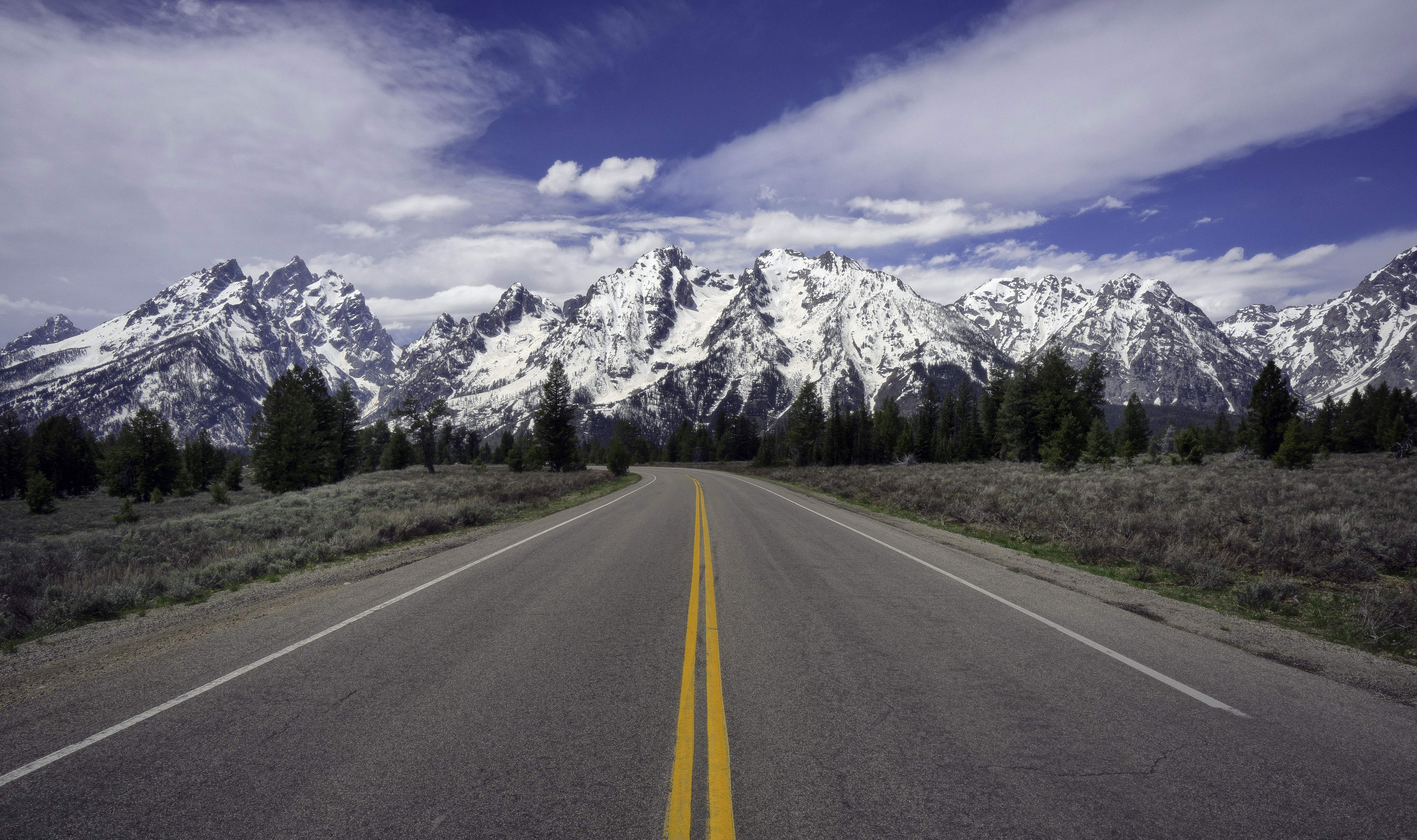 Empty road leading toward the snow-capped mountains in Jackson Hole valley.