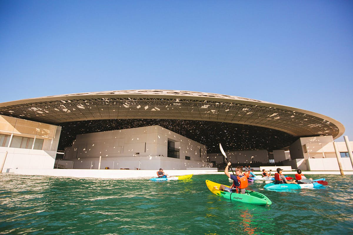 Travelers can kayak around the Louvre Abu Dhabi at sunrise and sunset