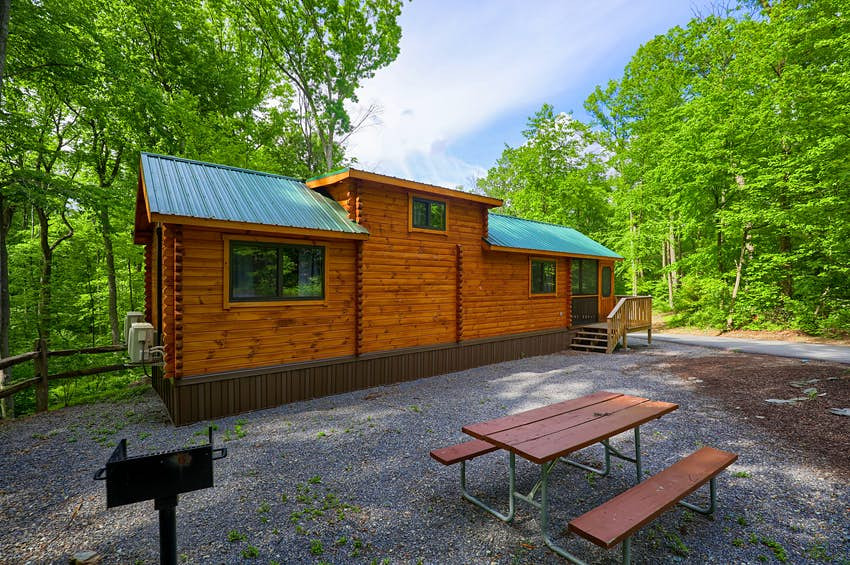 A cabin in a gravel lot with a grill at Yogi Bear's Jellystone Park Camp-Resort: Quarryville