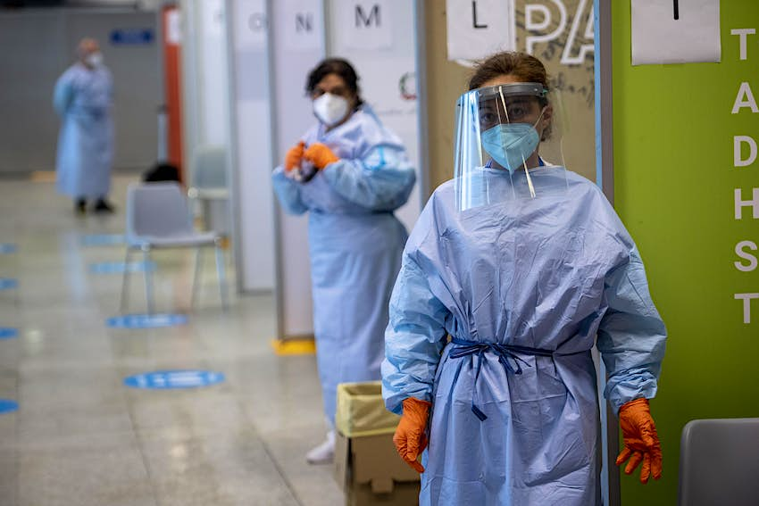 Health workers wait for passengers arriving from high-risk countries to carry out rapid antigenic tests for Covid-19 at a testing station in Rome Airport