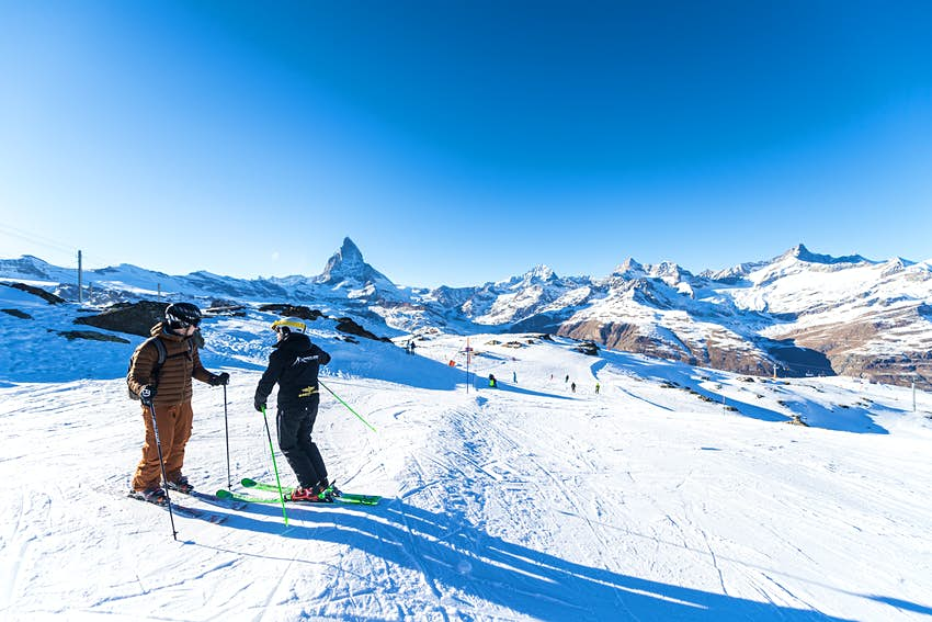 An instructor speaks to a skier as they stand at the top of a slope.