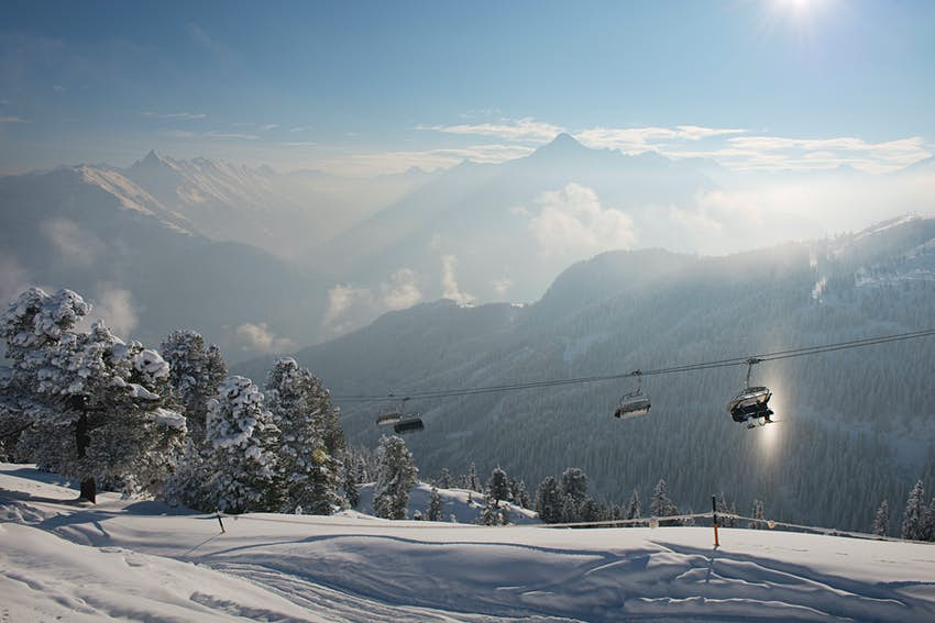 A very snowy ski slope with a silhouette of cable cars