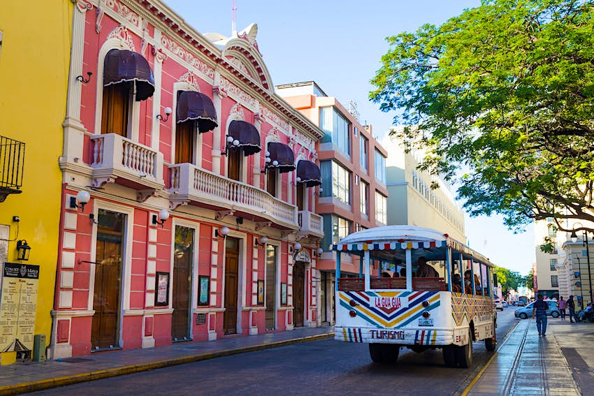 A tourist bus passes by the colorful facades of the picturesque town of Merida