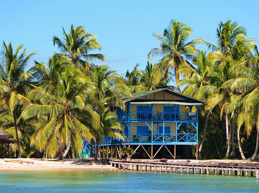 Tropical beach house with coconut trees and a dock, Caribbean side of Panama, Central America
