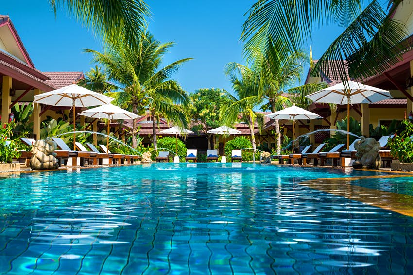 An empty swimming pool at a resort, surrounded by white sun loungers and palm trees