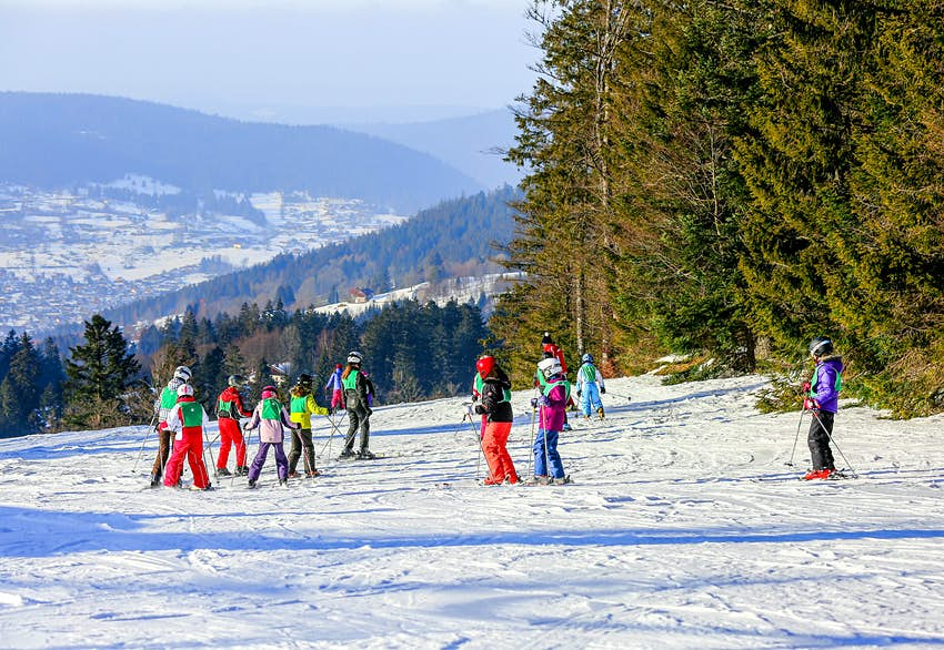 A group of children in full ski gear are led out by an instructor on the snow-covered slopes