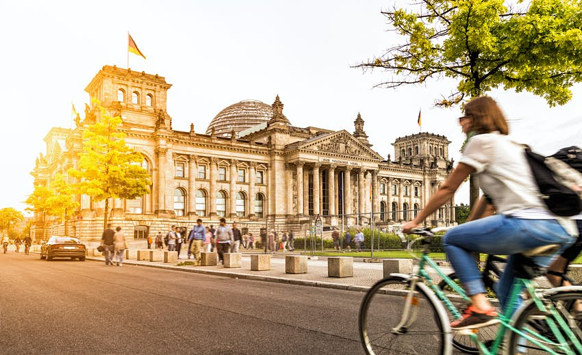 Two people ride bikes on the road, passing a large government building, the Reichstag, in Berlin