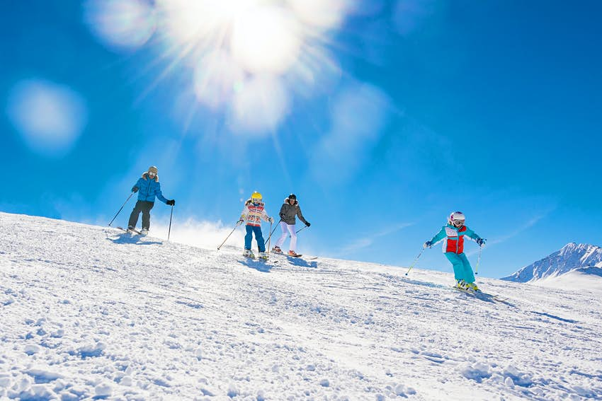 A group of two adults and two children ski down a slope together