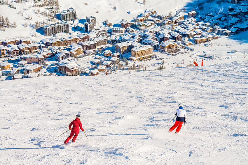 Two skiers viewed from behind as they descend a slope towards a town