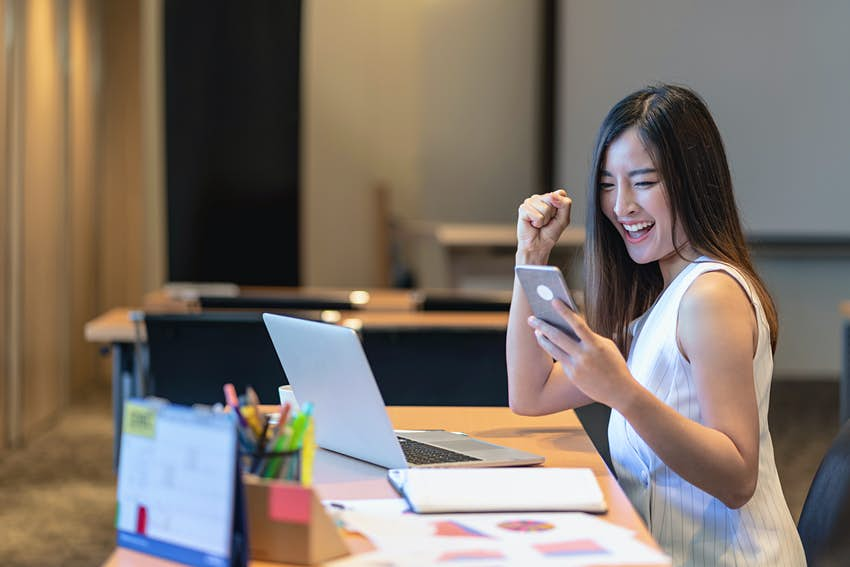 Business and lifestyle concept, Asian businesswoman in casual suit are glad when completed doing online shopping via smart mobile phone application or technology laptop in modern office