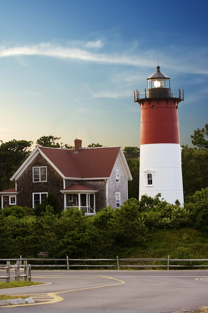 A red and white small lighthouse sits next to a cape cod house in front of a road.