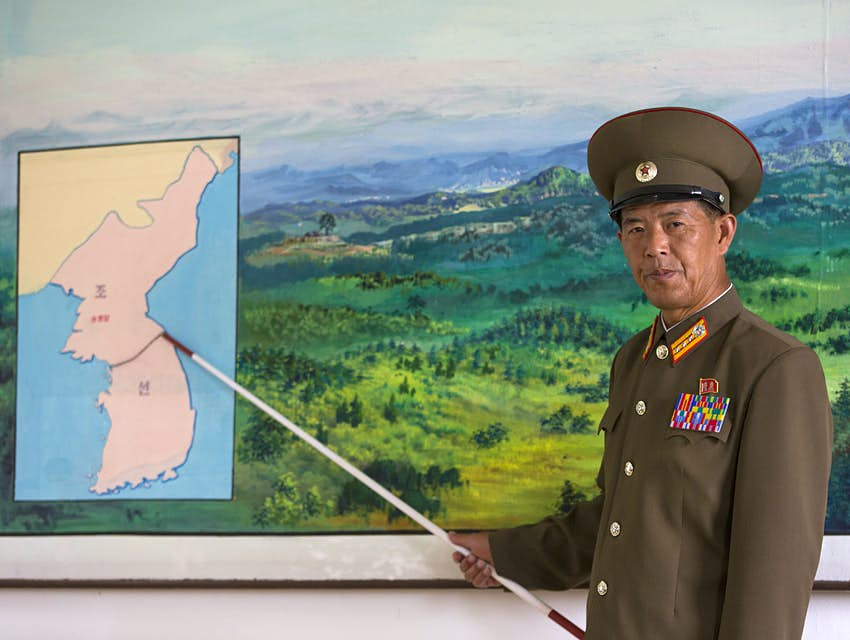 A stern-faced colonel using a stick to point to a map of the DMZ splitting North Korea