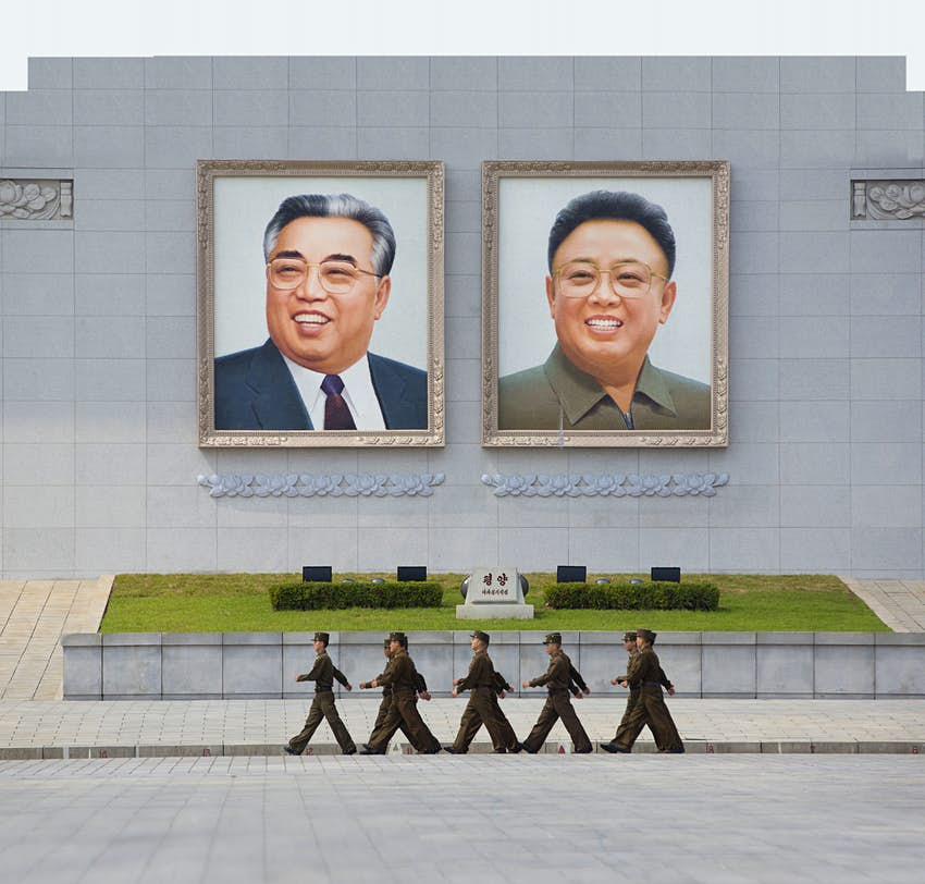 People's Army soldiers marching in front of giant portraits of Kim Il Sung and Kim Jong Il on Kim Il Sung Square
