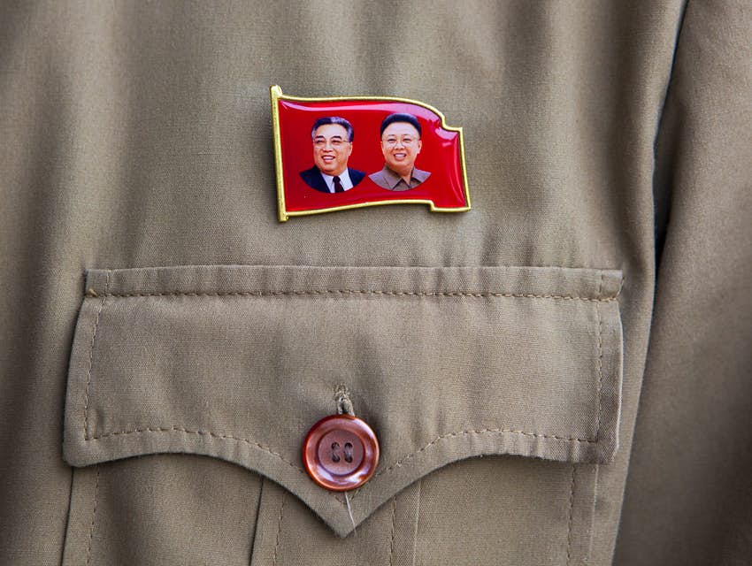 A pin in the shape of a red flag with Kim Jong-il and Kim Il-sung