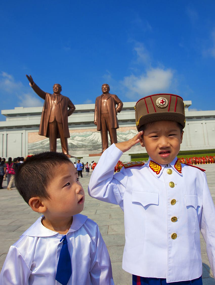 Two young boys in front of giant statues of  Kim Il Sung and Kim Jong-il in Grand Monument of Mansu Hill.