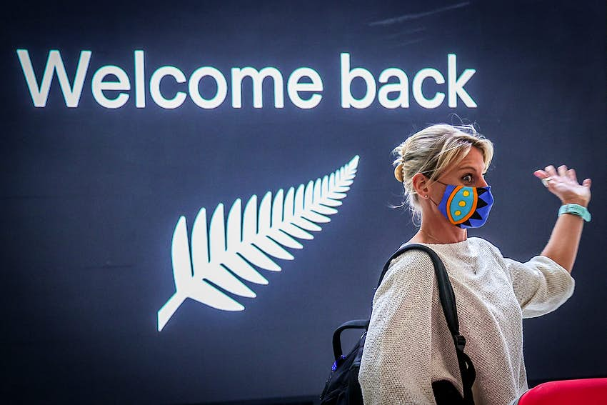 A passenger reacts upon arrival from New Zealand at Sydney International Airport