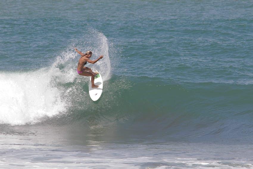 Una mujer surfea sobre una ola en Playa Hermosa