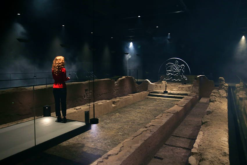An employee poses alongside a reconstruction of the Roman Temple of Mithras. It is dark but the stone is illuminated by warm light.