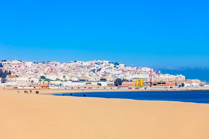 Une longue étendue de sable doré s'étend sur des kilomètres alors que l'eau d'un bleu vif pousse contre les rives.  Au loin, vous voyez la ville de Tanger.