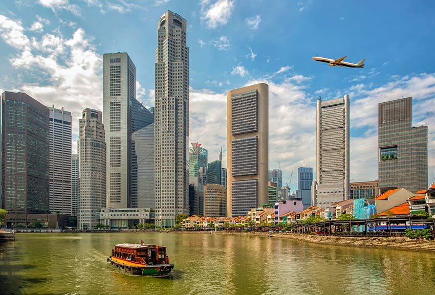 A plane flies over downtown Singapore's skyline with a ferry on the river below
