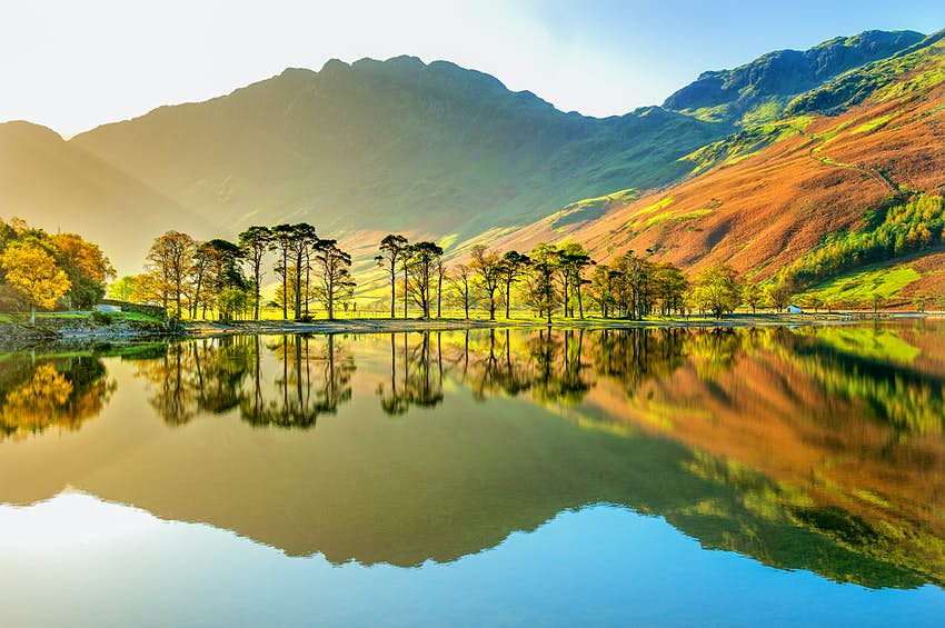Lake with a reflection of the surrounding mountains during the early morning.