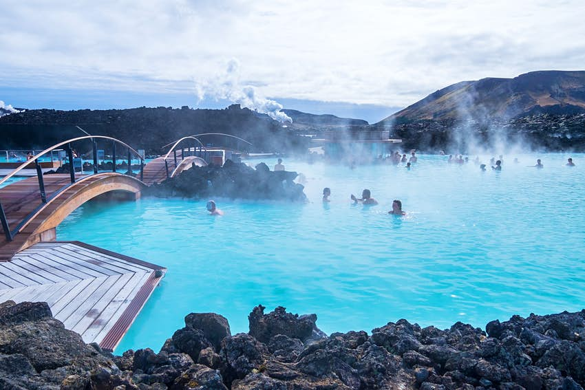 A huge outdoor swimming pool complex with very blue water and steam evaporating from it. It's surrounded by black volcanic rocks