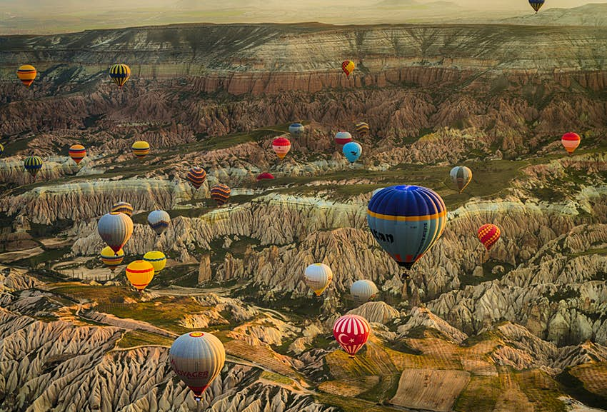 Aerial shot of brightly colored hot air balloons over a landscape with a lot of hills, exposed rock, and other geological features