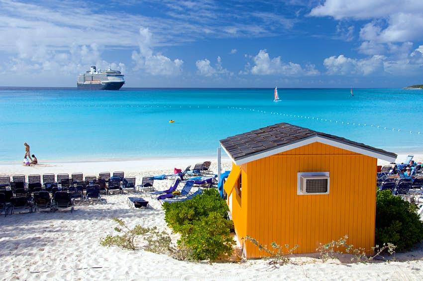 A colourful beach cabana with the Holland America cruise ship Westerdam in background at Half Moon Cay, Bahamas, Caribbean.