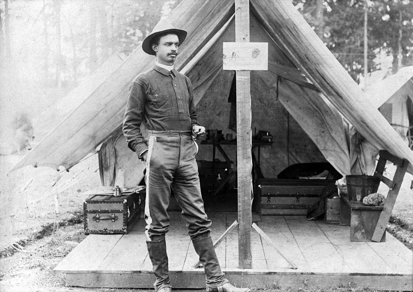Buffalo soldier. T.R. Clarke, 8th US Volunteer Infantry, standing in front of tent, during the Spanish-American War. ca. 1898