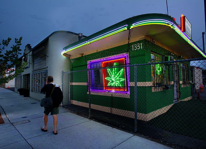 A man walks past a cannabis dispensary with a glowing pot leaf sign