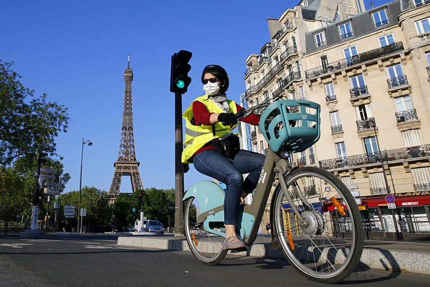 A woman wearing a protective mask rides her bicycle next to the Eiffel Tower as the lockdown continues due to the coronavirus outbreak (COVID 19) on April 23, 2020 in Paris, France.