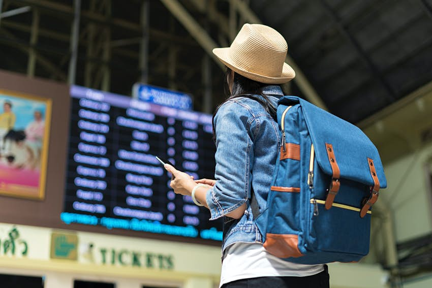 Young female backpacker checking her train arrival on a digital timetable board.