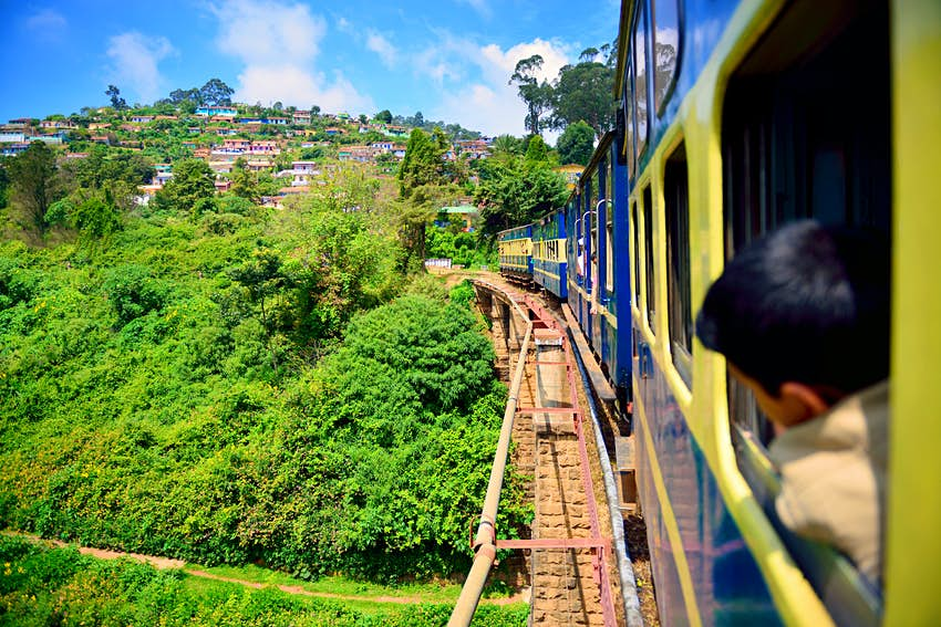 A train crossing a bridge curves through lush green hillsides in India