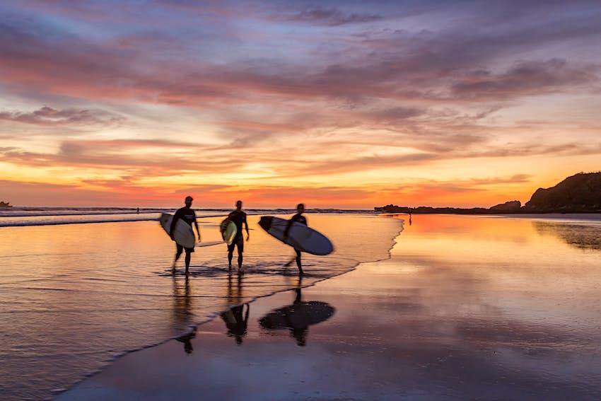 Surfistas al atardecer caminando por la playa, Costa Rica.