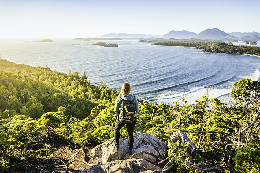 Elevated view of female hiker looking out from coastal forest, Pacific Rim National Park, Vancouver Island, British Columbia, Canada