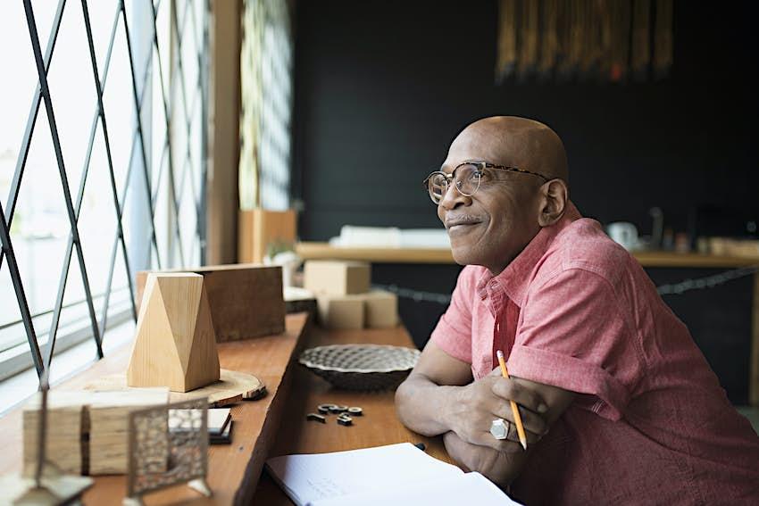Pensive senior male entrepreneur looking out window