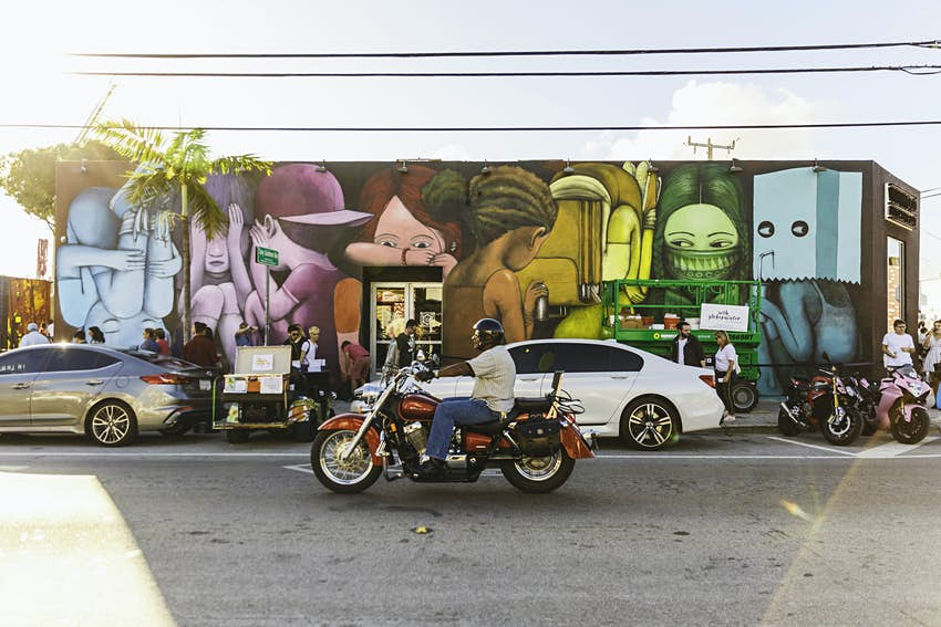 A motorcycle passes in front of a mural on the side of a building