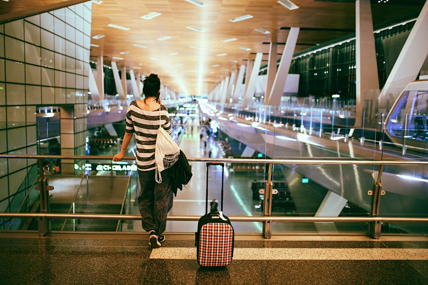 Young woman with a suitcase stands with her back to the camera in an empty airport terminal