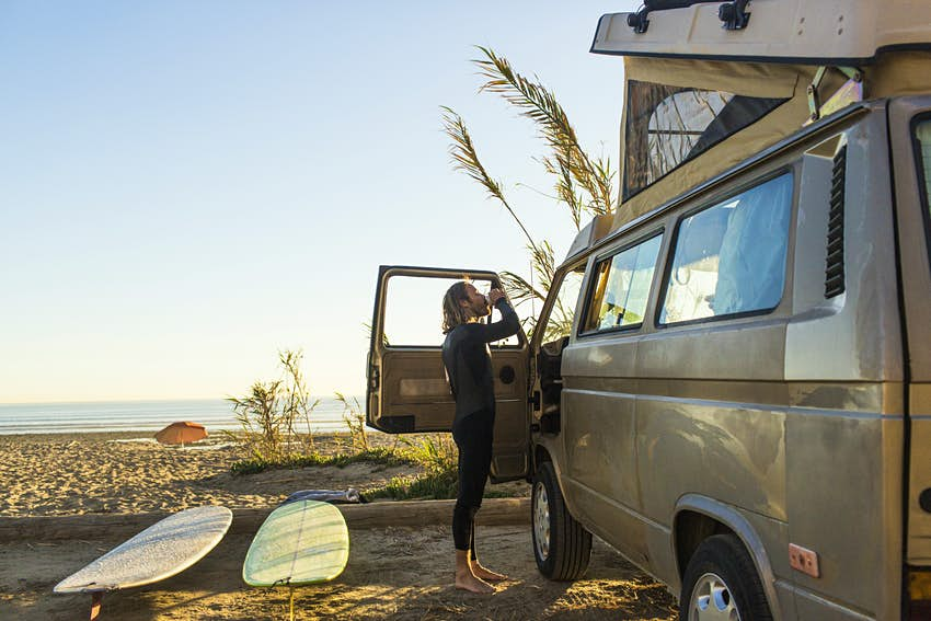 Side view of male surfer having drink outside mini van on San Onofre State Beach