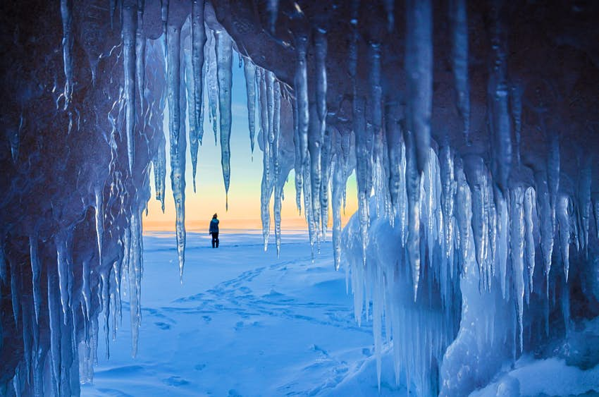 A shot looking out from the mouth of a cave towards a snowy landscape.  The cave is covered with ice cubes