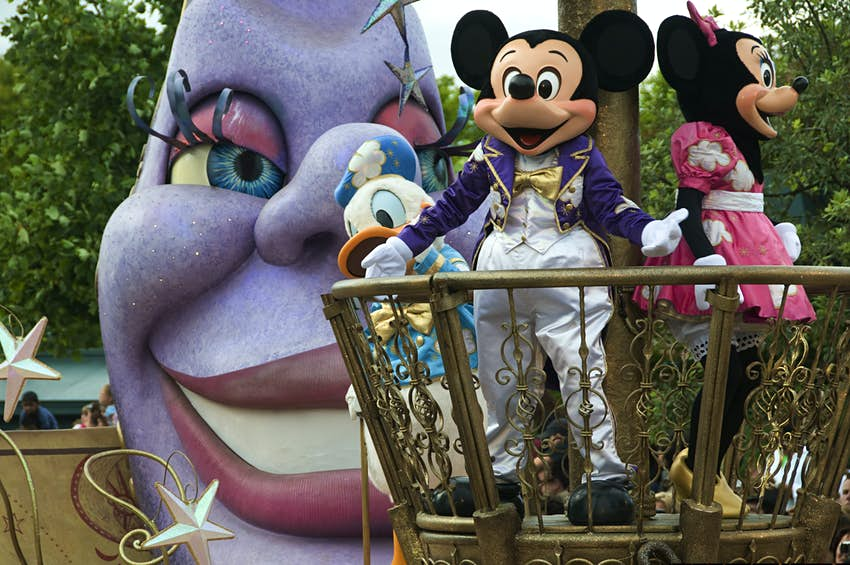 Iconic Disney mice characters, Mickey and Minnie, stand on a round platform with big open-mouthed smiles stuck on their faces
