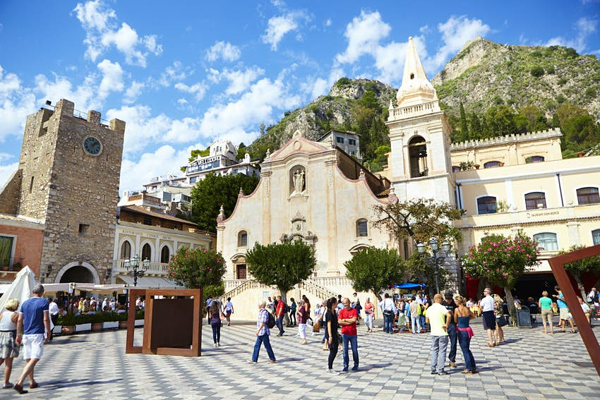 An Italian piazza dotted with people and an ornate church with a mountain in the background