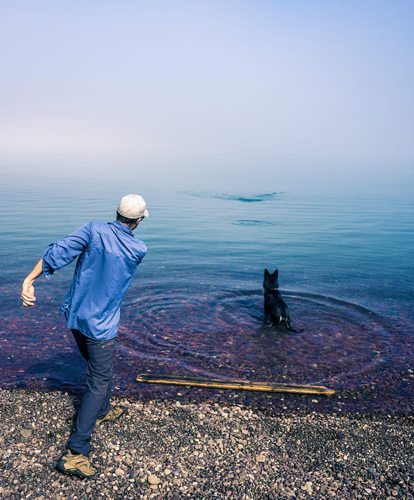 A man and his dog on the shore of Lake Superior, Michigan