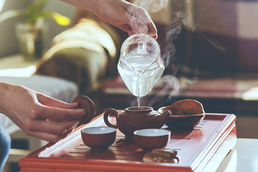 The tea ceremony. The woman pours hot water into the teapot with tea
