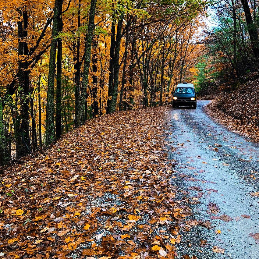 A camper van drives on a road surrounded by red, orange and yellow fall colors in Tennessee