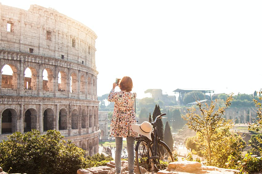 Beautiful young woman in colorful fashion dress alone on a hill with bike takes pictures of colosseum in Rome using smartphone camera at sunset. Attractive tourist girl with elegant straw hat.