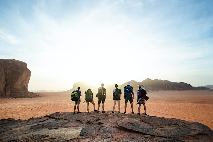 A group stands on the top of a rocky outcrop during sunset in Wadi Rum National Park.