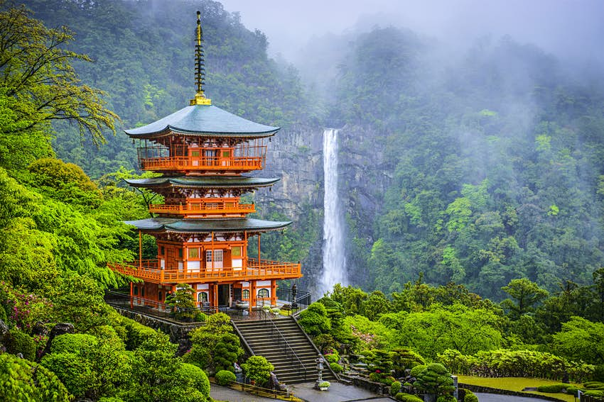 A red pagoda stands among thick green woodland, with a thin waterfall cascading down a rockface