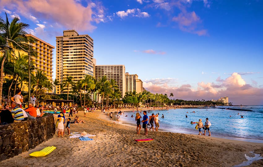 WAIKIKI, HI - APRIL 27 - Tourists on the beach front at sunset on Waikiki beach April 27, 2014 in Oahu. Waikiki beach is beachfront neighborhood of Honolulu, best known for white sand and surfing.