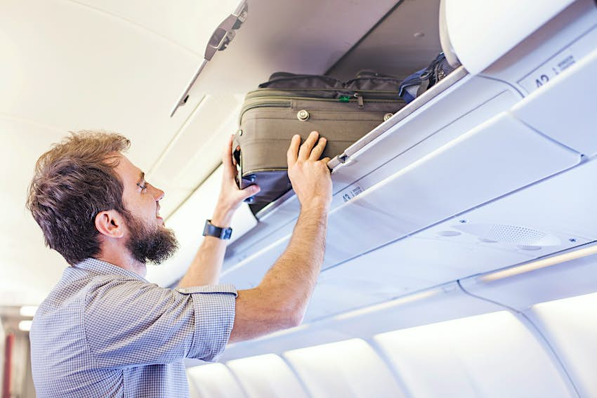 Man putting luggage in the hand-luggage compartment of an airplane.